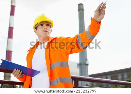 Male architect with clipboard at industry - stock photo