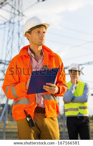 Male architect with clipboard working at site while coworker standing in background - stock photo