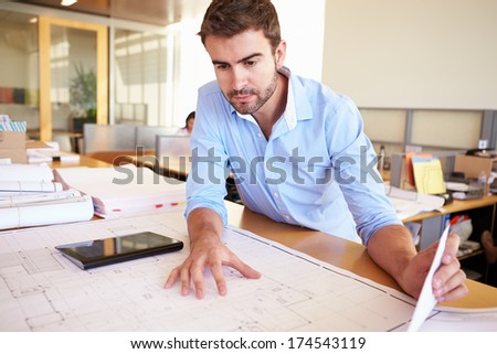 Male Architect With Digital Tablet Studying Plans In Office - stock photo