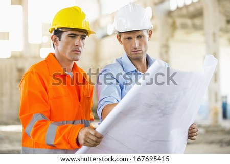 Male architects analyzing blueprint at construction site - stock photo