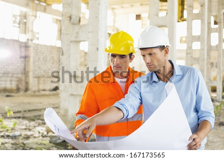Male architects discussing over blueprint at construction site - stock photo