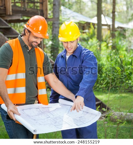 Male architects discussing over blueprint at construction site