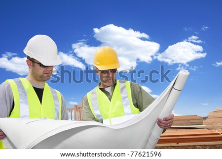 Male Architects looking at a blueprint Outdoors - stock photo