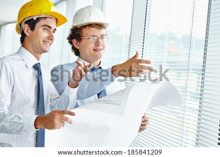 Male architects looking through window while discussing sketch of new construction