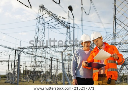 Male architects reviewing documents together at electric power plant - stock photo