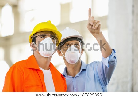 Male architects wearing protective mask while working at construction site - stock photo