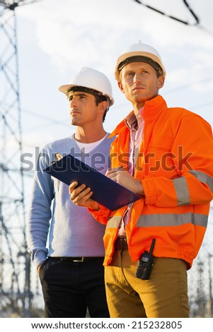 Male architects with clipboard inspecting site together - stock photo