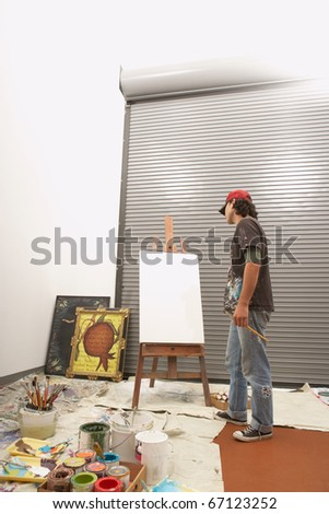 Male artist considering a blank easel - stock photo
