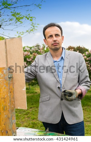 Male artist outdoors looking through the park  working  on a trestle and easel painting with oils and acrylics during an art class - stock photo