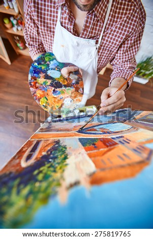 Male artist painting with oil paints on canvas - stock photo