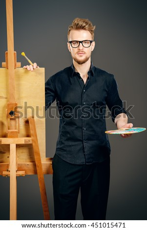 Male artist paints on an easel in the workshop. Occupation. - stock photo