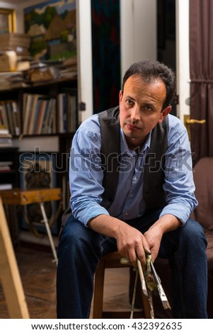 Male artist  sitting painting in a studio or gallery holding  paintbrushes - stock photo