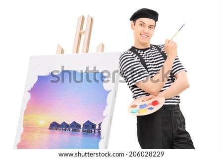 Male artist standing by a painting on an easel isolated against white background - stock photo