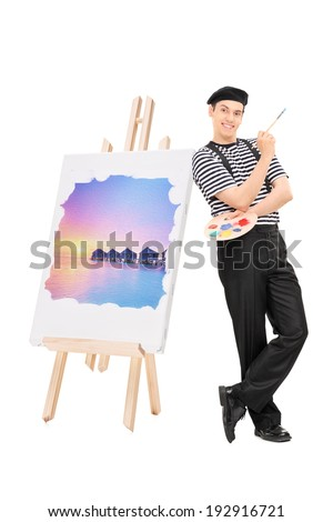 Male artist standing by a painting on an easel isolated on white background - stock photo