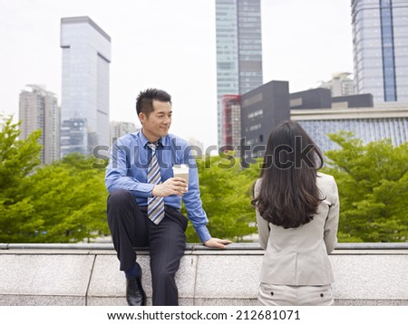male asian business executive talking to female colleague. - stock photo