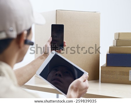 male asian courier company worker using cellphone and tablet computer to scan information on packages. - stock photo