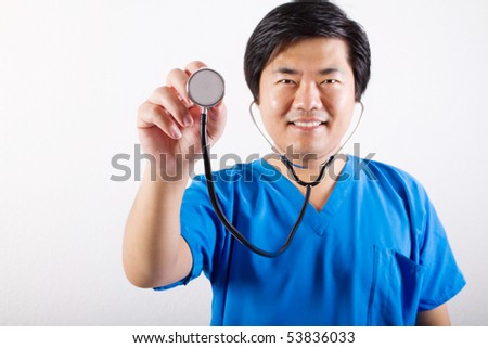 male Asian doctor holding a stethoscope - stock photo