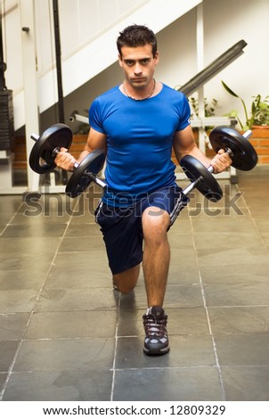 Male athelete / weightlifter, looking straight into camera, doing lunges and curls with dumbbell weights in his hands. - stock photo