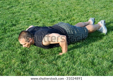 Male athlete doing push ups on the grass on a sunny afternoon. - stock photo