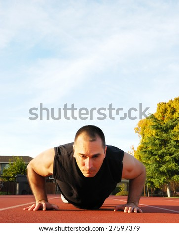 Male athlete doing push ups outdoors with blue sky and white clouds in the background. - stock photo