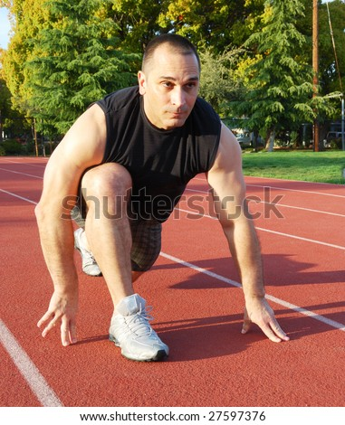 Male athlete getting ready to run on an athletic track with trees in the background on a sunny day. - stock photo