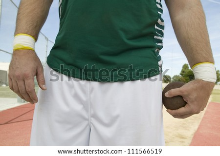 Male athlete holding metal ball on track - stock photo