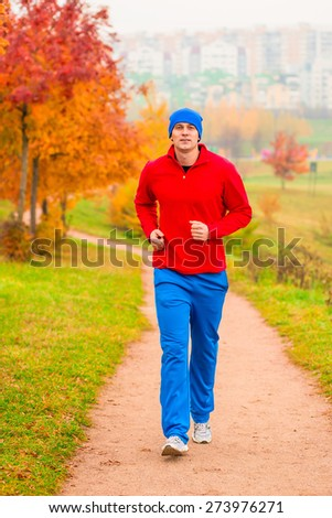Male athlete jogging in the morning in the park - stock photo