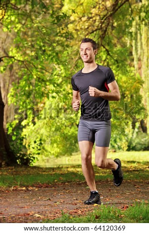 Male athlete jogging on a trail in the park - stock photo
