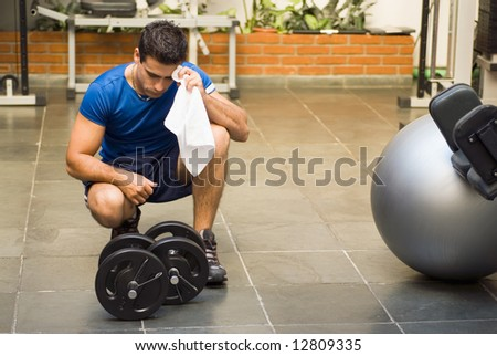 Male athlete kneeling down by dumbbells toweling sweat of his brow. - stock photo