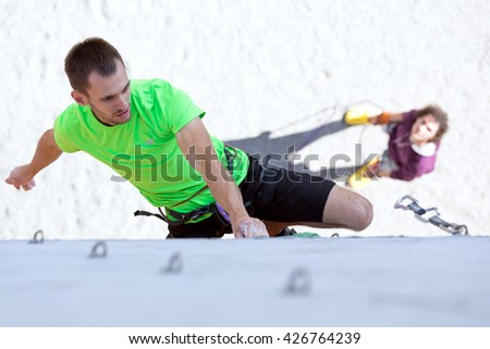 Male Athlete moving up on vertical climbing Wall and his belaying Partner staying on Background. National Climbing Championship, Dnipro, Ukraine, May 20, 2016, Male semifinal, Lead climbing - stock photo