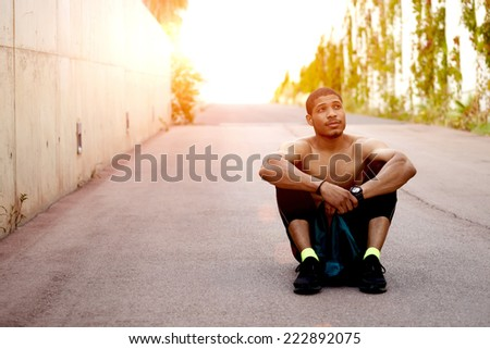 male athlete resting after cross fit exercise, sittinig on the road - stock photo