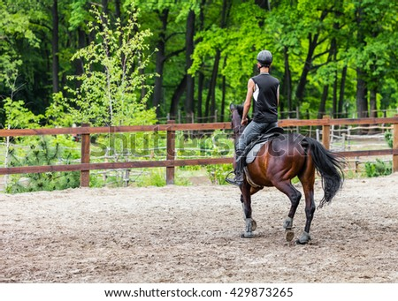 male athlete rides on horse, exercise outdoors