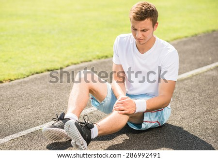 Male athlete runner touching foot in pain due to sprained ankle. - stock photo