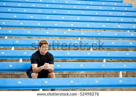 Male athlete sitting in the bleachers - stock photo