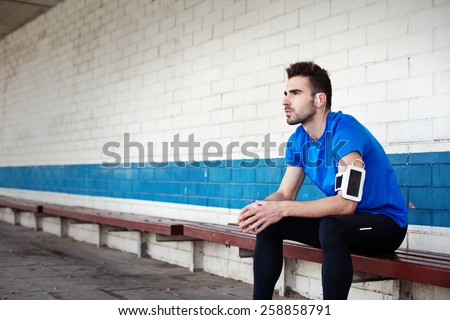 male athlete sitting on the bench and looking far away - stock photo