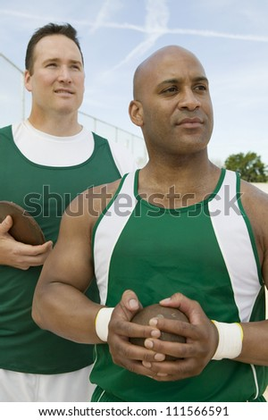 Male athletes holding shot put and discus while looking away - stock photo