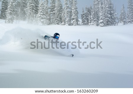 Male back-country free-rider in deep powder snow spraying a wave of snow - stock photo