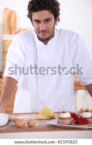 Male baker making sweet cakes - stock photo