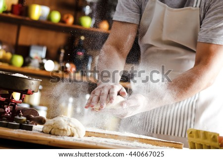 Male baker prepares bread. Male baker slaps on dough. Making bread.