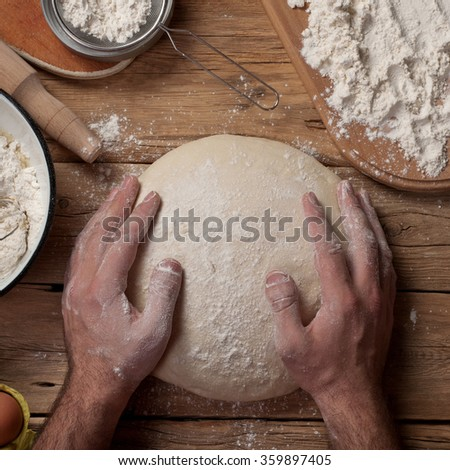 Male baker prepares bread on a wooden table in a bakery closeup. Top view. Copy space. Square frame - stock photo