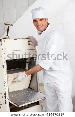 Male Baker Using Bread Slicer At Bakery