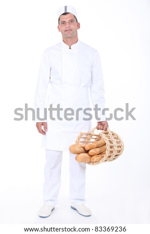 Male bakery worker with basket of bread - stock photo