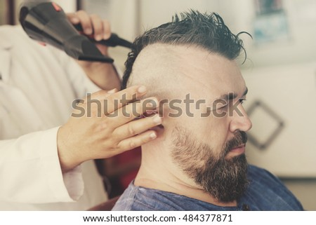 Male barber dry head using a hair dryer of a adult man with a mohawk