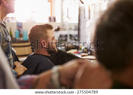 Male Barber Giving Client Haircut In Shop - stock photo