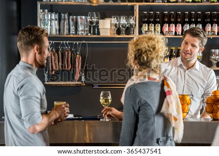Male bartender talking with customers at bar counter - stock photo