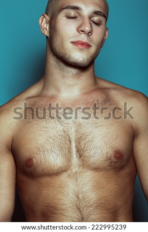 Male beauty concept. Dreaming handsome male model posing over blue background. Perfect skin, shaved head, hairy muscular body. Close up. Fashion studio portrait - stock photo