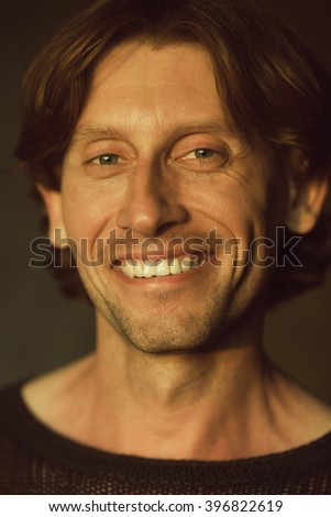 Male beauty concept. Emotional portrait of laughing handsome man in black knitted sweater posing over brown background. Glossy long hair, shiny perfect smile. Close up. Indoor shot - stock photo