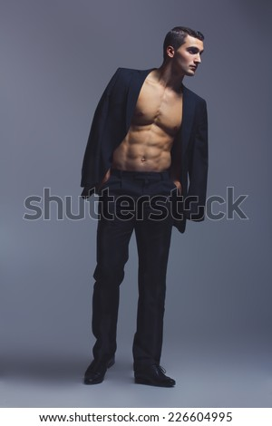 Male beauty concept. Fashionable and undressed young man in black classic suit with stylish haircut posing over gray background. Perfect hair & skin. Vogue style. Close up. Studio shot - stock photo