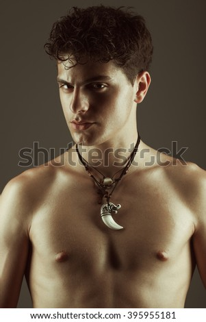 Male beauty concept. Handsome muscular male model in trendy ethnic necklace posing over brown background. Perfect glossy hair, healthy clean skin. Close up. Fashion studio portrait