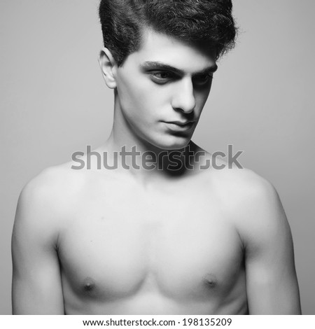 Male beauty concept. Handsome muscular male model posing over light-gray background. Perfect glossy hair and healthy clean skin. Vogue style. Close up. Fashion studio portrait